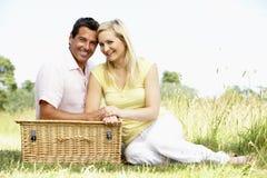 Jeunes couples ayant le pique-nique dans la campagne Image libre de droits