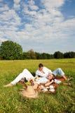 Jeunes couples ayant le pique-nique dans le pré Images stock