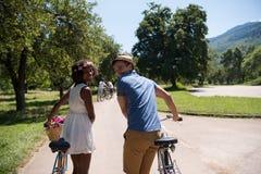 Jeunes couples ayant le tour joyeux de vélo en nature Image libre de droits