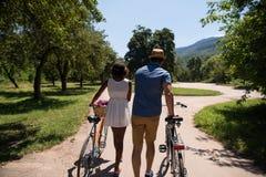 Jeunes couples ayant le tour joyeux de vélo en nature Image stock