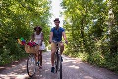 Jeunes couples ayant le tour joyeux de vélo en nature Photo stock