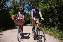 Jeunes couples ayant le tour joyeux de vélo en nature Photographie stock