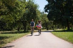 Jeunes couples ayant le tour joyeux de vélo en nature Images stock