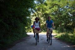 Jeunes couples ayant le tour joyeux de vélo en nature Photos stock