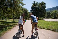 Jeunes couples ayant le tour joyeux de vélo en nature Images libres de droits