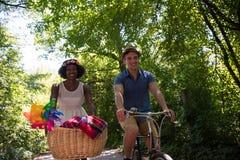 Jeunes couples ayant le tour joyeux de vélo en nature Photo libre de droits