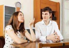 Jeunes couples ayant parler sérieux à la table Images libres de droits