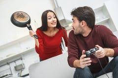 Jeunes couples ayant romantique égalisant à la maison l'épouse irritée avec la casserole image stock