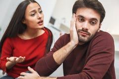 Jeunes couples ayant romantique égalisant à la maison le malentendu Photographie stock libre de droits