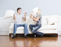 Jeunes couples ayant un combat d'oreiller sur le sofa image libre de droits