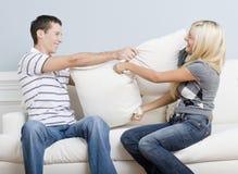 Jeunes couples ayant un combat d'oreiller sur le sofa photos libres de droits