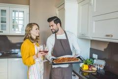 Jeunes couples ayant un verre de vin image stock
