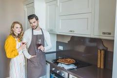 Jeunes couples ayant un verre de vin photos stock