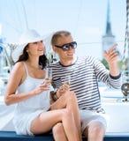 Jeunes couples ayant une partie sur un bateau à voile de luxe à l'été Photographie stock libre de droits