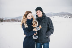 Jeunes couples ayant une promenade avec leur chien dans la campagne neigeuse Image stock