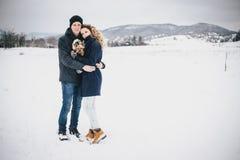 Jeunes couples ayant une promenade avec leur chien dans la campagne neigeuse Photo stock