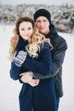 Jeunes couples ayant une promenade dans la campagne neigeuse Photos stock