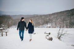 Jeunes couples ayant une promenade dans la campagne neigeuse Images stock