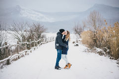 Jeunes couples ayant une promenade dans la campagne neigeuse Images libres de droits
