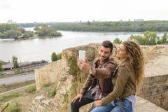 Jeunes couples beaux prenant un selfie près de la rivière Images libres de droits