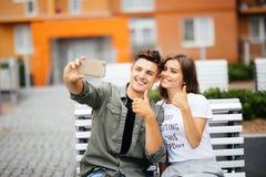 Jeunes couples beaux se reposant sur le banc au centre de la ville et prenant un selfie avec des pouces  Amour et tendresse durée Photos libres de droits