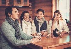 Jeunes couples buvant du thé chaud dans la cuisine de cottage d'hiver Photographie stock
