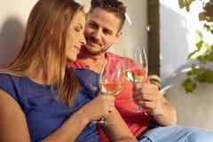Jeunes couples célébrant avec du vin blanc ensemble Photo stock