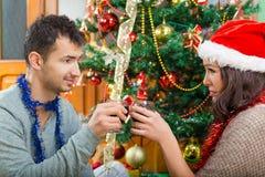 Jeunes couples célébrant Noël à la maison avec des verres de vin Photo libre de droits