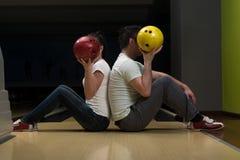 Jeunes couples cachant leurs visages derrière la boule de bowling Photographie stock