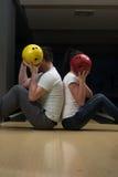 Jeunes couples cachant leurs visages derrière la boule de bowling Photo stock