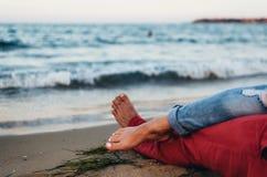 Jeunes couples caressant sur la plage près de l'eau Jambes enlacées, photographie stock libre de droits