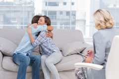 Jeunes couples caressant sur le divan Photo stock