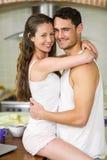 Jeunes couples caressant sur le plan de travail de cuisine Photographie stock libre de droits