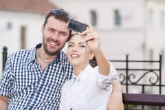 Jeunes couples caucasiens dans l'amour se reposant sur le banc dehors Image stock