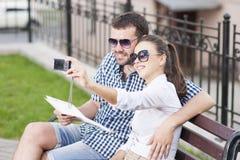 Jeunes couples caucasiens dans l'amour se reposant sur le banc dehors Photos libres de droits