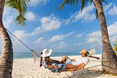 Jeunes couples caucasiens dans l'hamac en Maldives, plage tropicale photographie stock
