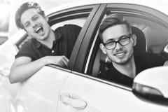 Jeunes couples caucasiens dans la voiture ayant l'amusement sur le voyage par la route images stock
