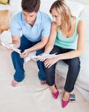 Jeunes couples caucasiens regardant des factures sur le sofa image libre de droits