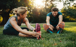 Jeunes couples caucasiens s'exerçant en parc Image stock