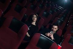 Jeunes couples caucasiens se reposant dans la salle de cinéma Images libres de droits