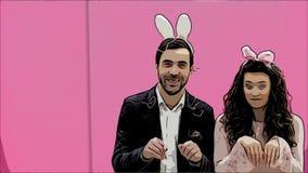 Jeunes couples charismatiques sur le fond rose Avec les oreilles rabattues sur la tête Pendant le ceci, la personne feint pour fu banque de vidéos