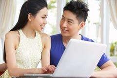 Jeunes couples chinois au bureau et à l'ordinateur portatif d'utilisation Images libres de droits
