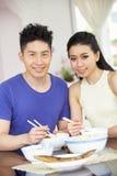 Jeunes couples chinois se reposant à la maison mangeant le repas Image libre de droits