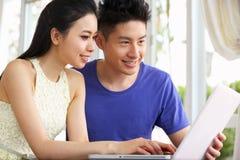 Jeunes couples chinois se reposant utilisant l'ordinateur portatif à la maison photos libres de droits