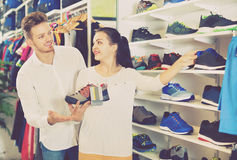 Jeunes couples choisissant de nouvelles espadrilles dans le magasin de sports Photos libres de droits