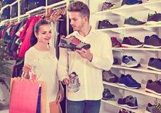 Jeunes couples choisissant de nouvelles espadrilles dans le magasin de sports Photos stock
