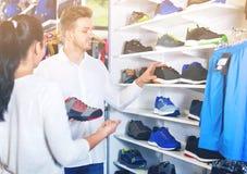 Jeunes couples choisissant de nouvelles espadrilles dans le magasin de sports Images stock