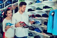 Jeunes couples choisissant de nouvelles espadrilles dans le magasin de sports Photo stock