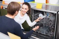 Jeunes couples choisissant la nouvelle machine à laver la vaisselle dans le sto d'appareils Images libres de droits