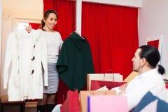 Jeunes couples choisissant le manteau à la boutique Photos libres de droits
